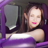 Woman drives purple car Stock Photography
