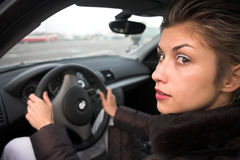 Woman driving. Pretty woman driving a car hands on the wheel, looking at left side Royalty Free Stock Images