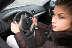 Woman driving. Pretty woman driving a car hands on the wheel, looking at left side Stock Photography