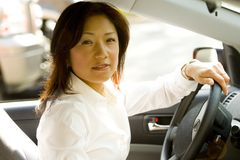 Woman driving. A portrait of a middle-aged Asian woman driving a car Stock Image
