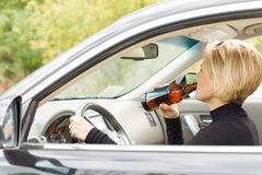 Woman driving along drinking alcohol. View through the side window of a woman driving along in her car drinking alcohol from the bottle and posing a threat to royalty free stock image