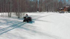 Woman driving on ATV along the forest on the snow track. Drone stock video