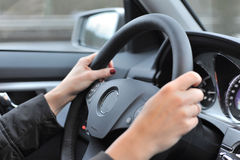Woman driving car. Details of woman holding car steering wheel Royalty Free Stock Photo