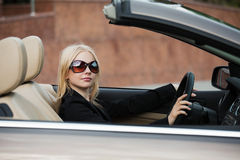 Young fashion woman in sunglasses driving car Royalty Free Stock Images