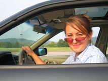 Woman Driving Car. Woman wearing sunglasses driving a car Royalty Free Stock Images