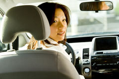 Woman driving car. A portrait of a middle-aged Asian woman driving a car royalty free stock photos