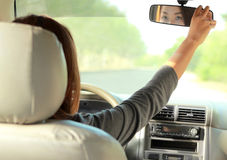 A woman driving a car while adjusting the rearview mirror Stock Photos