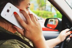 Woman driving car on cellphone Stock Images