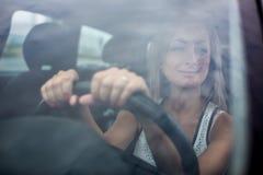 Woman driving a car - female driver at a wheel of a modern car Stock Photos