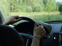 Woman driving car, hand hold steering wheel. Female hands with a gold bracelet on the steering wheel of a car while driving. Against the background, the royalty free stock photo