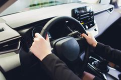 Woman driving a car, hands on steering wheel close-up. royalty free stock images