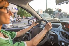 Woman driving car with hands on steering wheel. Interior close up, selective focus, side view, motion blurred on street. Woman driving car with hands on Royalty Free Stock Photos