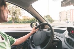 Woman driving car with hands on steering wheel. Interior close up, selective focus, side view, motion blurred on street. Woman driving car with hands on Stock Image