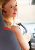 Woman driving car with headset Royalty Free Stock Photos