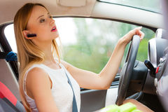 Woman driving car with headset Royalty Free Stock Images