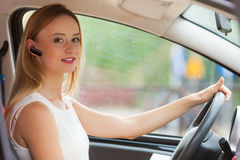 Woman driving car with headset. Transport and safety concept. Young blonde woman driving car using her mobile phone and headset, side view stock image