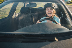 Woman driving car in helmet with horror on her face Stock Photography