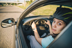 Woman driving car in helmet with horror on her face Royalty Free Stock Image
