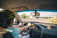 Woman driving car in helmet with horror on her face Stock Photo