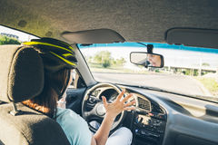 Woman driving car in helmet with horror on her face Royalty Free Stock Photos