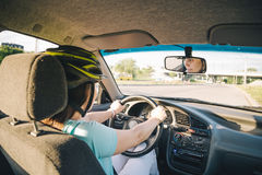 Woman driving car in helmet with horror on her face Royalty Free Stock Photo