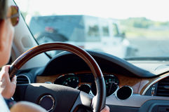 Woman Driving Car on Highway. Woman's hands on steering wheel driving down the highway Royalty Free Stock Photography