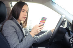 Woman driving a car and looking at her smartphone Stock Images