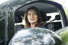 Woman driving car and looking outside Royalty Free Stock Photography