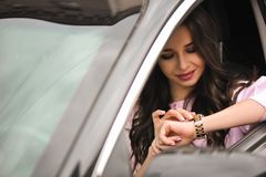 Woman driving a car and looking at watch stock photos
