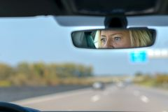 Woman driving a car on a motorway. With a view ahead through the windscreen and her eyes reflected in the rear view mirror stock photo