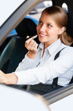 Woman driving the car and painting her lips Royalty Free Stock Image