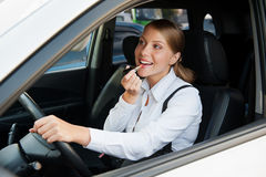 Woman driving the car and painting her lips Stock Images