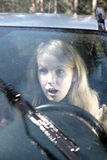 Woman driving a car in the rain. Frightened woman driving a car in the rain Stock Image