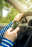 Woman driving car and reading received sms message on smartphone Royalty Free Stock Images