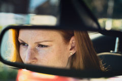 Woman Driving a Car - Reflection in the Mirror Stock Images
