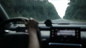 Woman driving car on rural road in forest stock footage