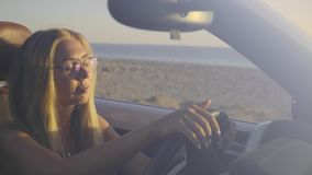 Woman Driving Car By The Sea. Smiling young blonde woman driving in convertible car along the coastal road in Greece. Front view of pretty hipster girl traveling stock footage