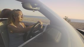 Woman Driving Car By The Sea. Smiling young blonde woman driving in convertible car along the coastal road in Greece. Front view of pretty hipster girl traveling stock video