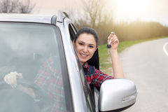 Woman driving car and showing keys. Young pretty woman showing keys through car window and expressing happiness, on the road Royalty Free Stock Image