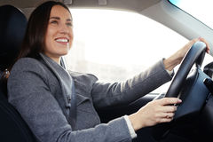 Woman driving a car and smiling Stock Photos
