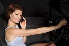 Woman driving car and talking on a cell phone Stock Images