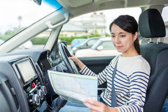 Woman driving car and using map Royalty Free Stock Photography