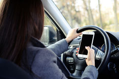 Woman driving car and using smartphone Stock Images