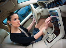 Woman driving and changing radio station. Woman changing radio station while driving car royalty free stock photos