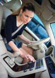 Woman driving and changing radio station. Woman changing radio station while driving car stock photo