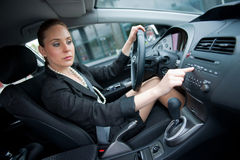 Woman driving and changing radio station. Woman changing radio station while driving car stock photography