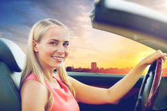 Woman driving convertible car over city sunset Stock Image