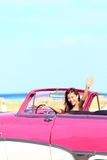 Woman driving convertible car waving happy stock photography
