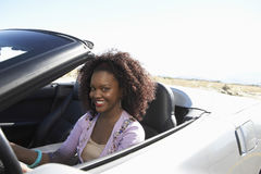 Woman Driving Convertible On Desert Road. Portrait of smiling African American woman driving convertible on desert road Stock Photo