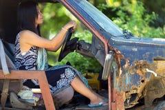 Woman driving damaged car Stock Photos